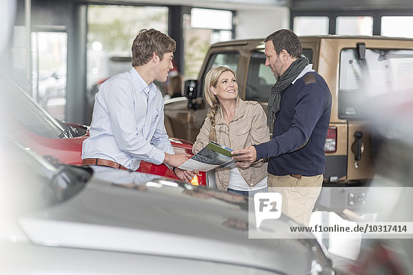Autohändler im Gespräch mit einem Paar im Showroom