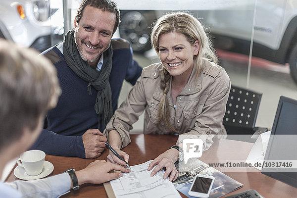 Paare unterzeichnen Kaufvertrag im Autohaus
