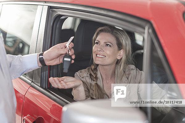 Frau sitzt im neuen Auto und erhält Schlüssel