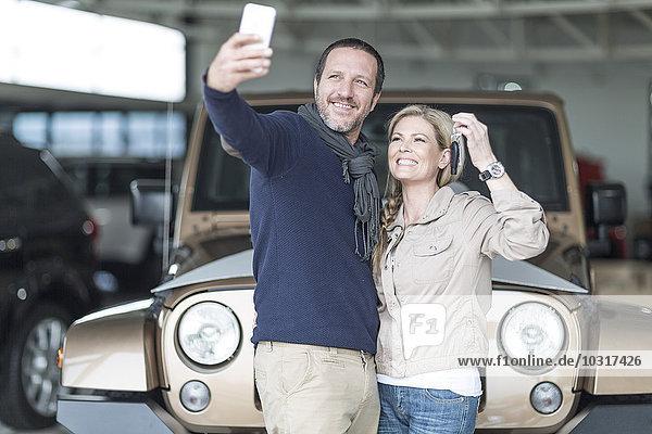 Glückliches Paar im Autohaus nimmt Selfie vor dem neuen Auto
