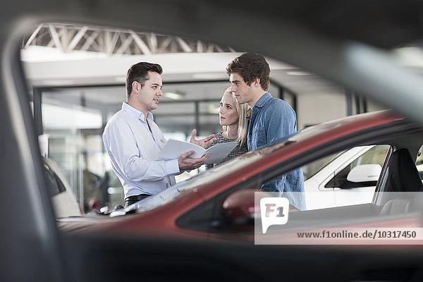 Autohändler zeigt dem jungen Paar eine Broschüre im Showroom