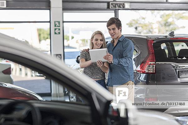 Junges Paar mit digitalem Tablett im Autohaus