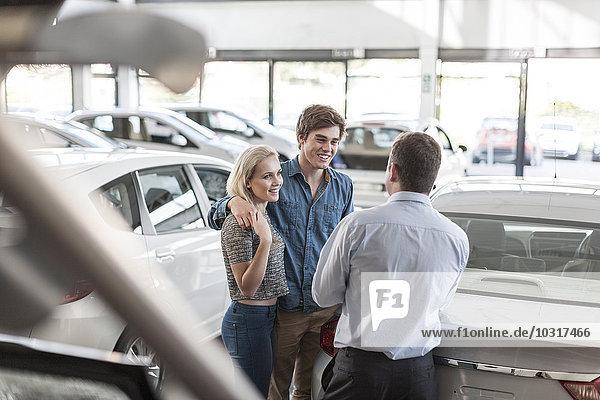 Autohändler im Gespräch mit einem jungen Paar im Showroom