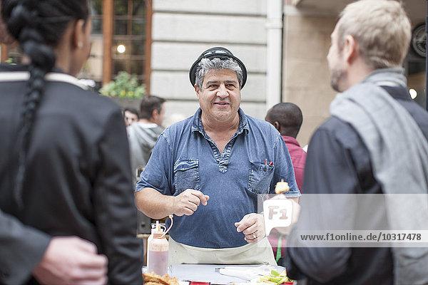 Lebensmittelverkäufer auf dem Stadtmarkt mit Snacks für Kunden