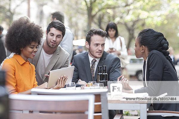 Kollegen mit digitalem Tablett im Außenrestaurant Kollegen mit digitalem Tablett im Außenrestaurant