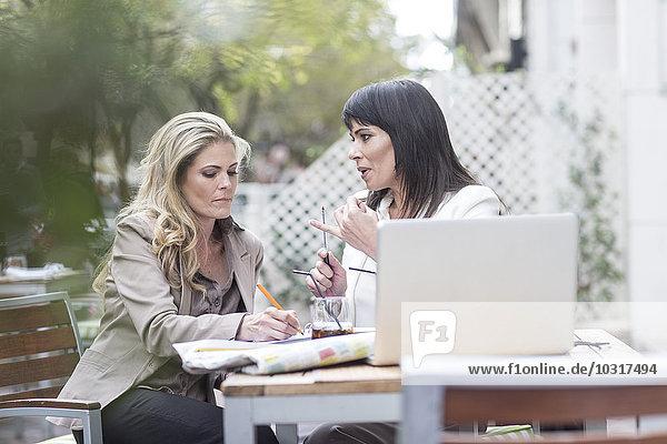 Zwei Frauen im Outdoor-Café mit Laptop  die sich Notizen machen.