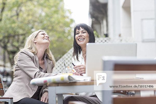 Zwei glückliche Frauen im Outdoor-Café Zwei glückliche Frauen im Outdoor-Café