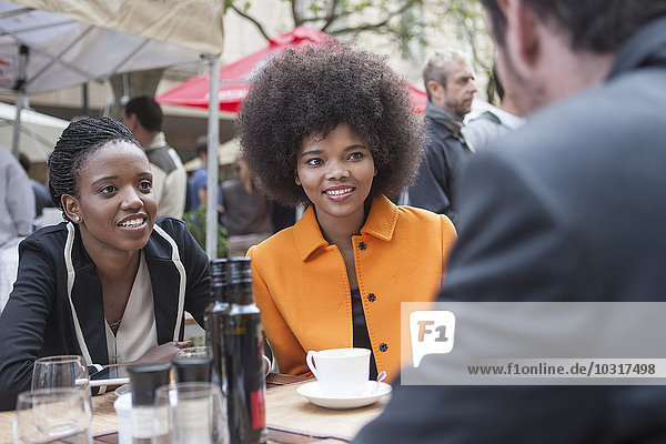 Kollegen im Außenrestaurant im Gespräch Kollegen im Außenrestaurant im Gespräch