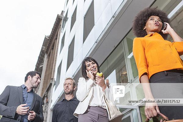 Vier Geschäftsleute  die mit zwei Geschäftsfrauen auf dem Handy spazieren gehen