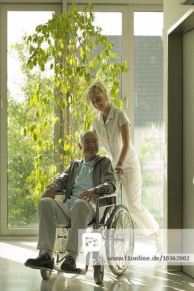 Senior Senioren Mann schieben Rollstuhl