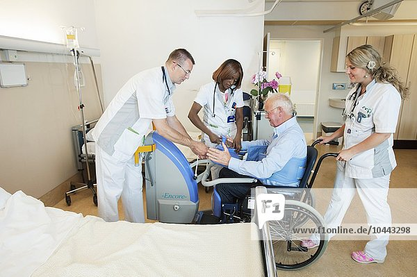 MODEL RELEASED. Nurses helping a patient out of bed and into a wheelchair with an active lifter. Nurses helping a patient out of bed