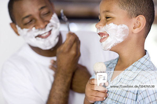 MODEL RELEASED. Fatherhood. Father and son with shaving foam on their faces. The father is shaving whilst his son is singing into a shaving brush. Fatherhood