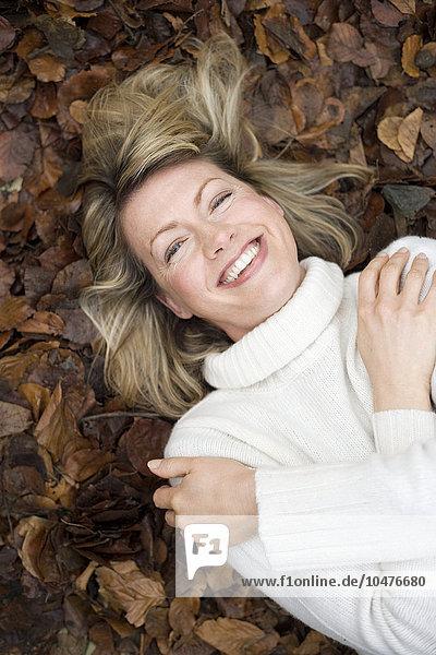 liegend liegen liegt liegendes liegender liegende daliegen Frau lächeln Laub