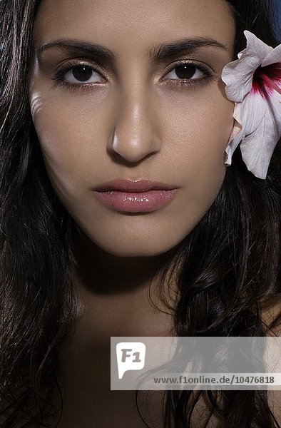 MODEL RELEASED. Healthy woman with a rosemallow flower (^IHibiscus sp.^i) in her hair. Healthy woman