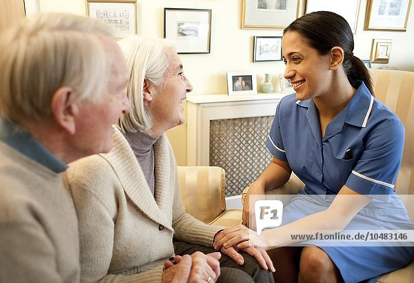 PROPERTY RELEASED. MODEL RELEASED. Home visit. Nurse visiting a senior couple in their home. Nurse on a home visit