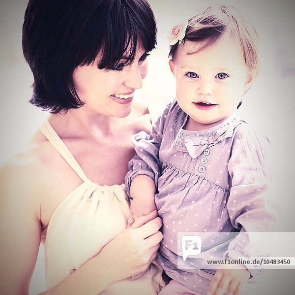 MODEL RELEASED. Mother and daughter. Mother holding her 15 month old daughter. Mother and daughter