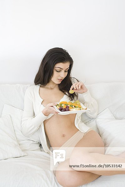 junge Frau junge Frauen Frucht Salat essen essend isst
