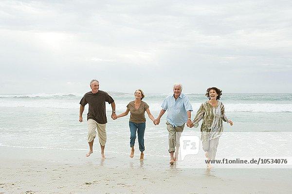 Vier ältere Erwachsene laufen am Strand entlang