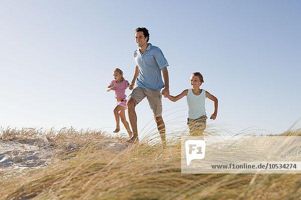 Vater und Kinder laufen auf Sanddüne