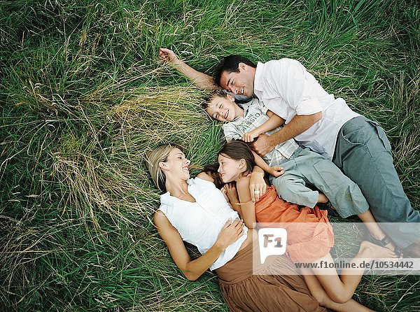 Familie auf dem Rasen liegend