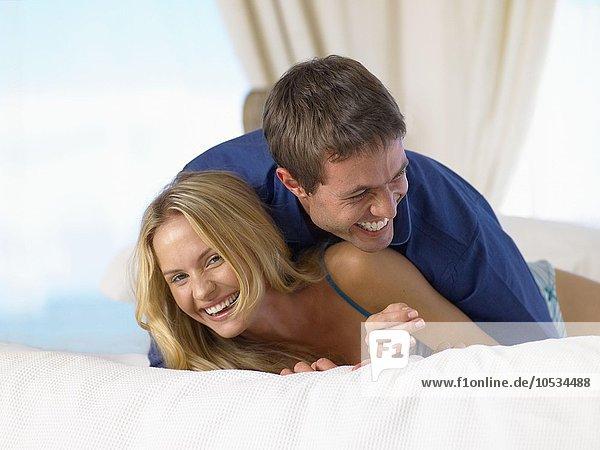 Pärchen lachend auf dem Bett