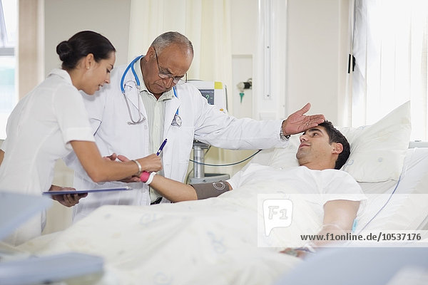 Arzt und Krankenschwester mit Krankenhauspatientin