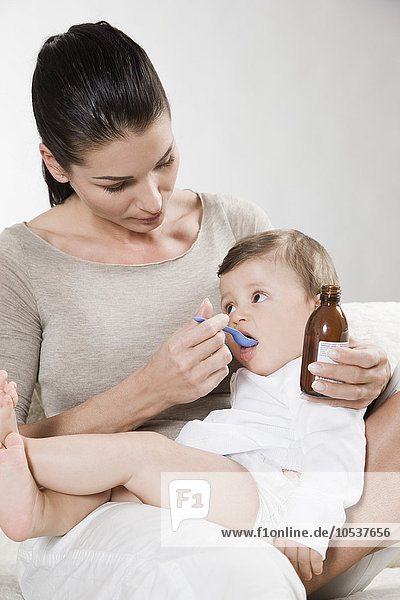 Mother gives syrup to sick baby