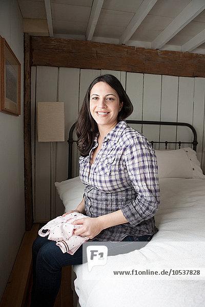werdende Mutter auf dem Bett sitzend