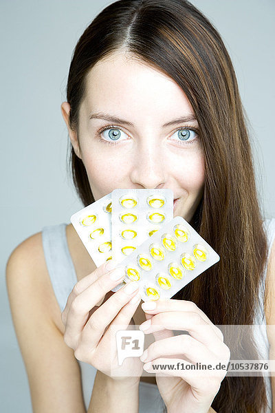 young woman holding capsules