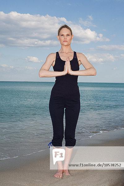 Mittlere erwachsene Frau in Yoga-Pose am Strand