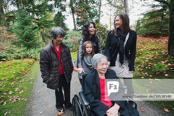 Mehrgenerationen-Familie schiebt ältere Frau im Rollstuhl