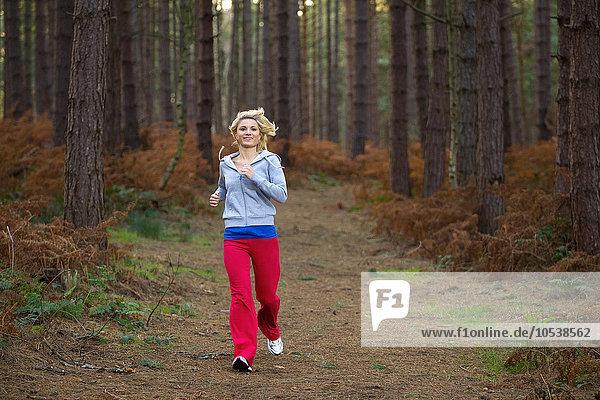 Lächelnde Frau  die im Wald rennt