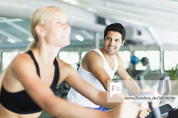 Couple using exercise machines in gym