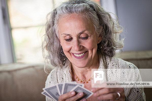 Seniorin beim Kartenspiel zu Hause