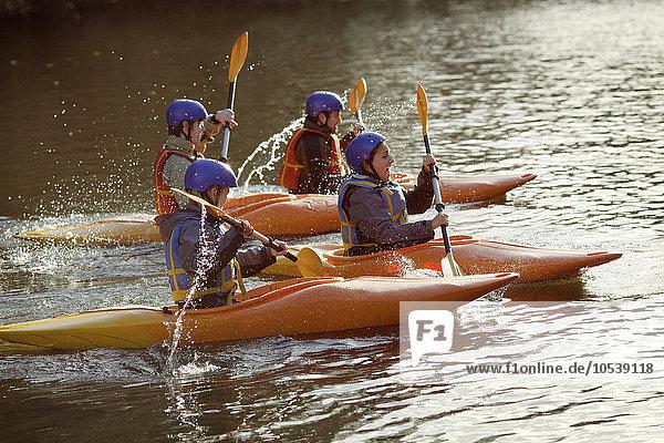 Kajakfahrer rudern zusammen auf dem stillen See