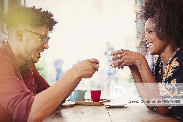 Paar trinkt Kaffee von Angesicht zu Angesicht im Cafe