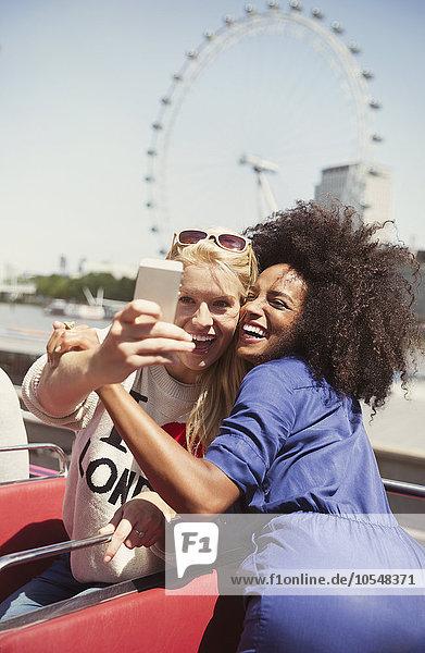Enthusiastische Freunde im Doppeldeckerbus mit London Eye im Hintergrund