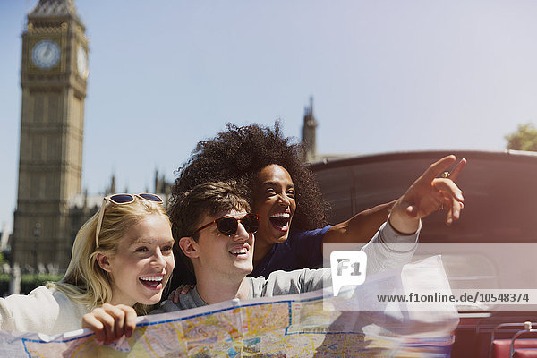 Enthusiastische Freunde mit Karte unter dem Big Ben-Uhrturm in London