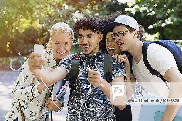 Freunde nehmen Selfie mit Fotohandy im Park mit.