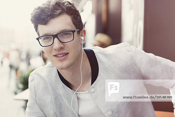 Porträt eines lächelnden Mannes mit Brille, der Musik über Kopfhörer hört.