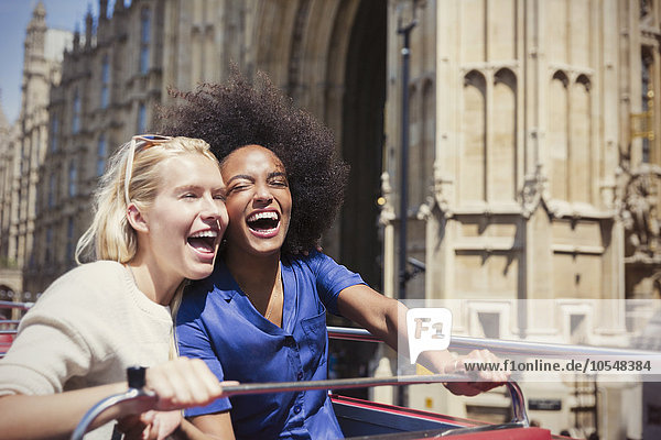 Begeisterte Freunde lachen im Doppeldeckerbus in London