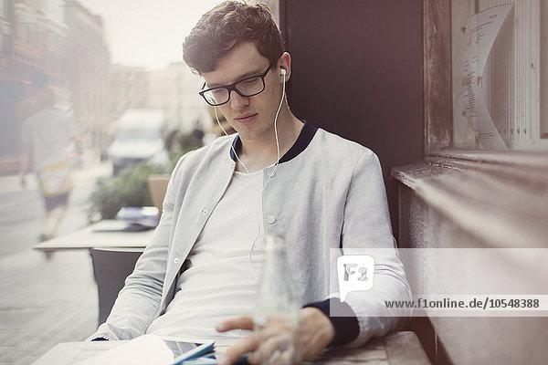 Junger Mann mit Brille und Kopfhörer mit digitalem Tablett im Straßencafé