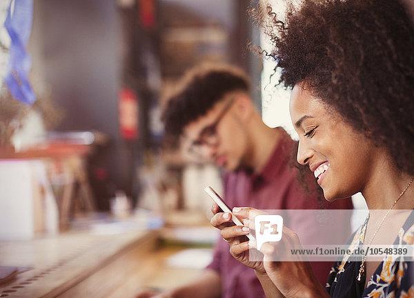 Lächelnde Frau SMS mit Handy