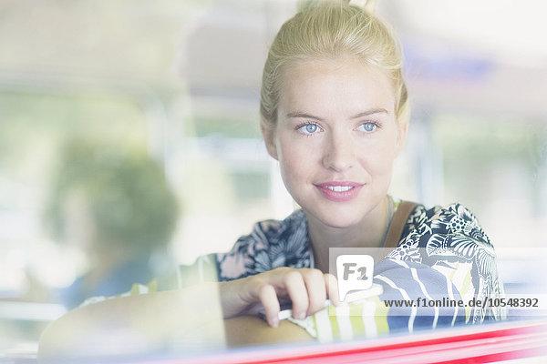 Blonde Frau mit Blick aus dem Fenster im Bus