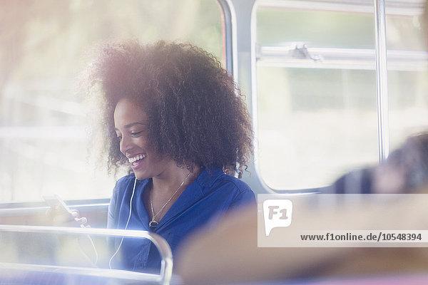 Lächelnde Frau mit Afro-SMS mit Handy im Bus
