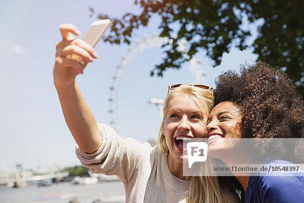 Freunde, die Selfie mit London Eye im Hintergrund nehmen, London, Großbritannien