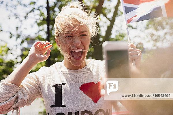 Enthusiastische Frau mit britischer Flagge beim Fotografieren