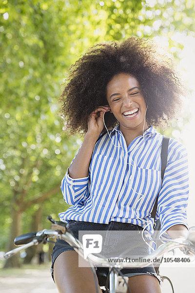 Enthusiastische Frau mit Afro-Fahrrad, die Musik über Kopfhörer hört.