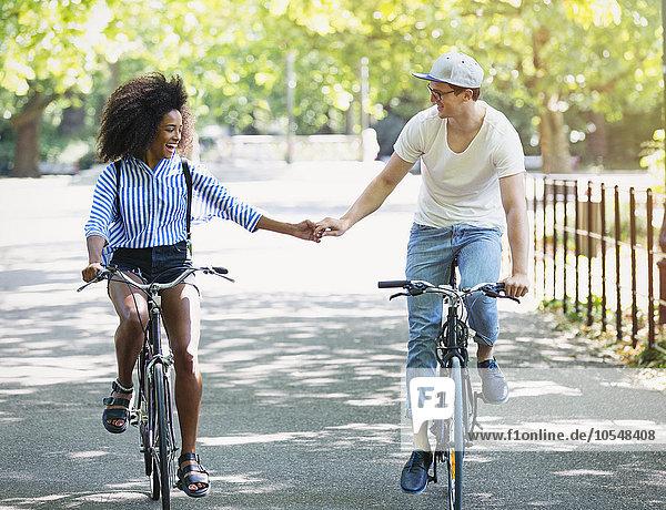 Paar hält Hände beim Fahrradfahren im Stadtpark
