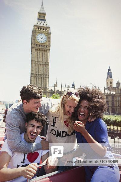 Enthusiastische Freunde im Doppeldeckerbus unter dem Big Ben-Uhrturm, London, Großbritannien